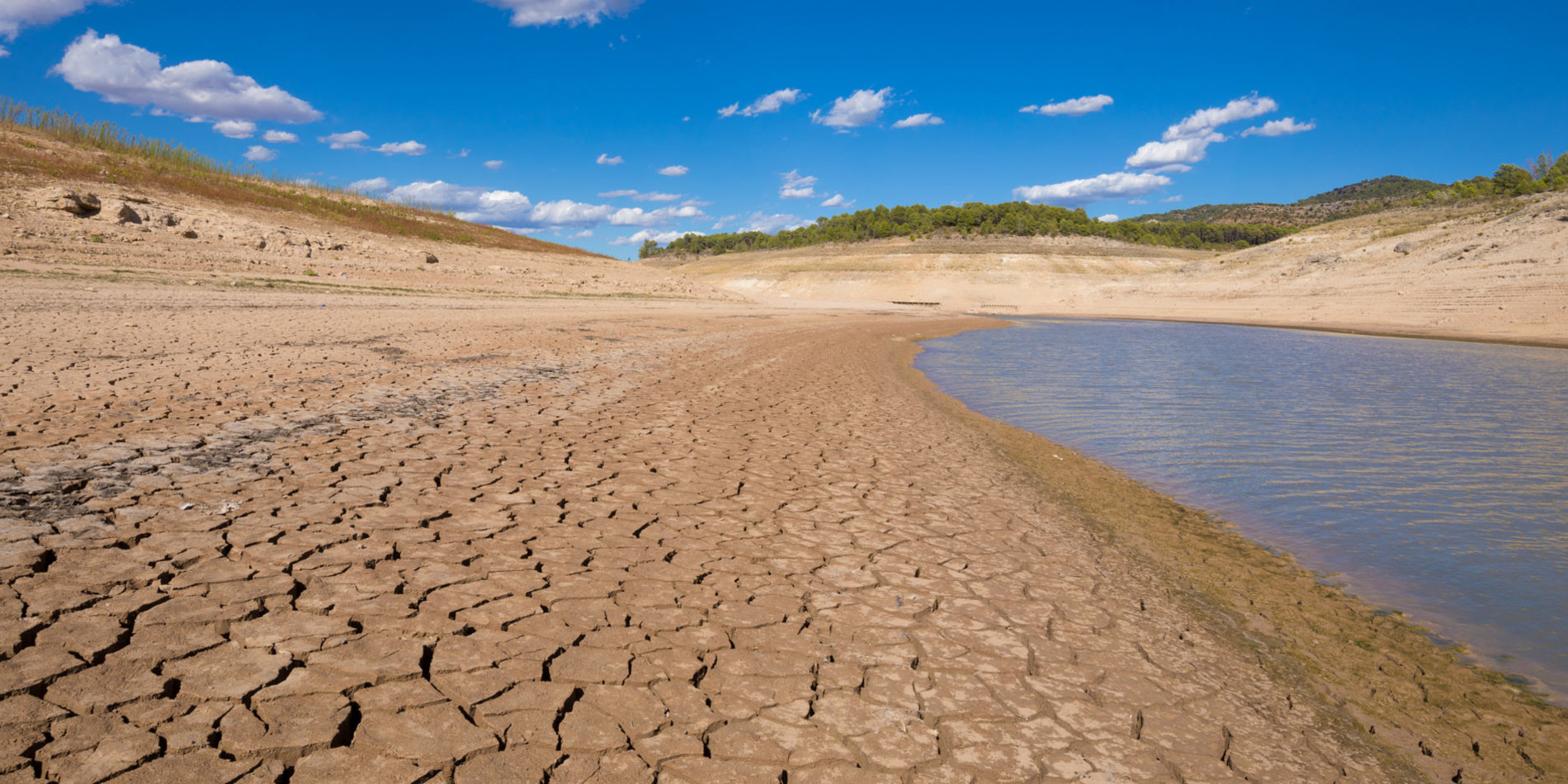 low level water and dry earth ground from extreme drought in the Entrepenas reservoir, in Guadalajara, Castile, Spain