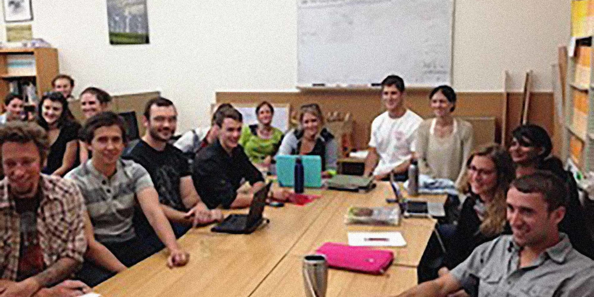 a group of smiling students sitting at a conference table