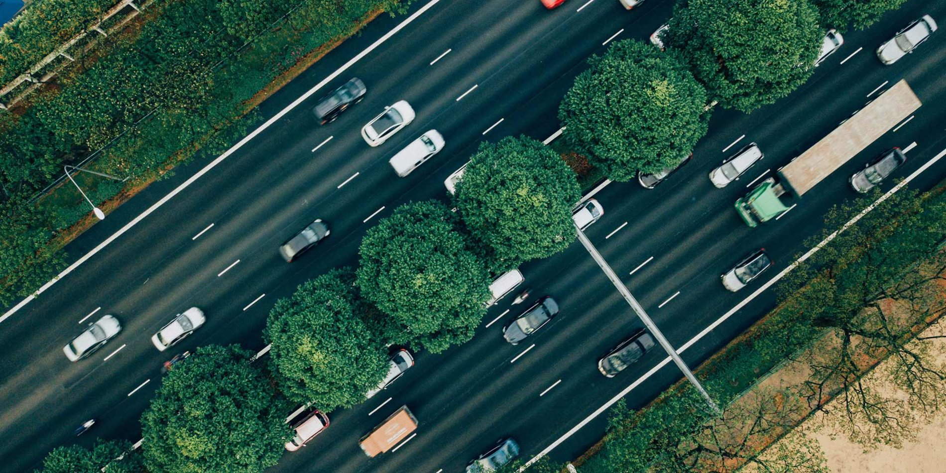 an aerial view of a road divided by a line of trees