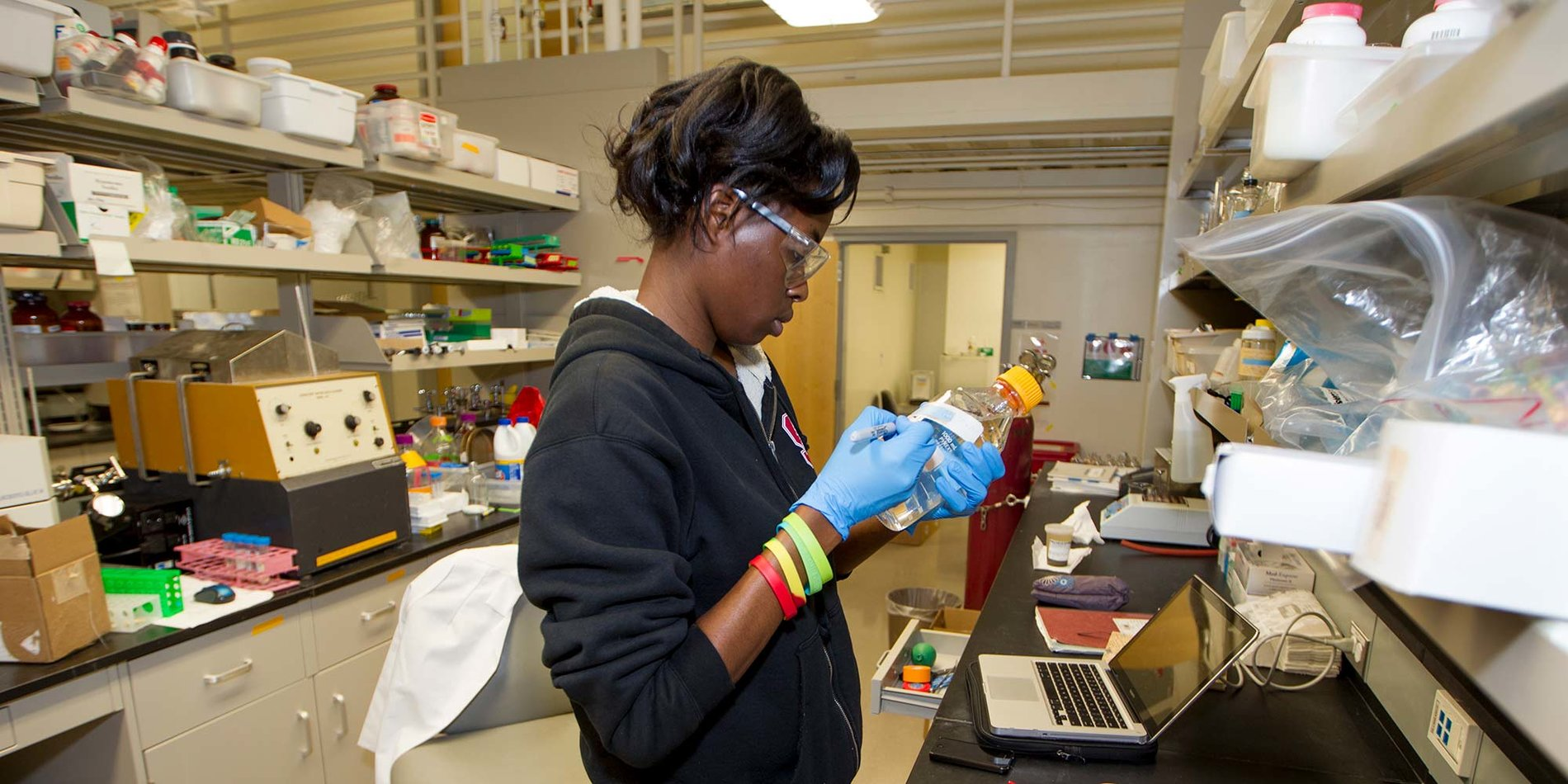a woman in a hoodie, wearing gloves, in a lab