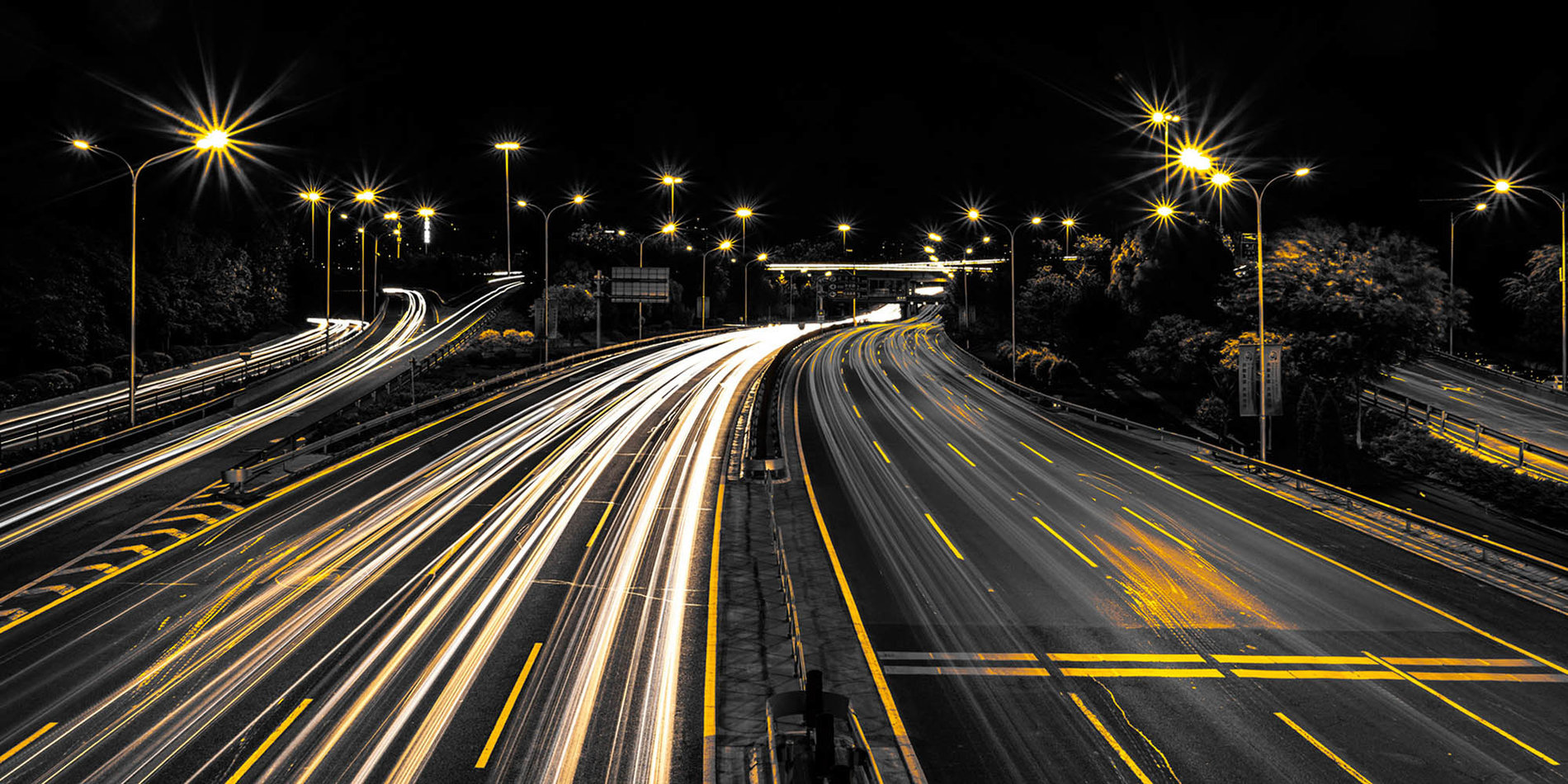 a long exposure photo of a highway illuminated by streaks of white lights from car headlights and yellow streetlamps