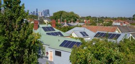 Suburban homes with rooftop solar panels, with a city in the distant background