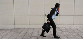 A businessman struggles in strong winds on the sidewalk of a city street in Tokyo